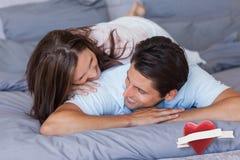 Sammansatt bild av par som har gyckel på sängen Arkivbilder