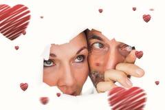 Sammansatt bild av par som ser till och med sönderrivet papper Royaltyfria Bilder