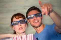 Sammansatt bild av par som tycker om en filmnatt Arkivbild