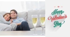 Sammansatt bild av par som vilar på en soffa med flöjter av champagne Royaltyfri Bild