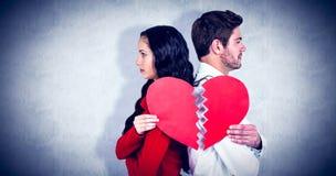 Sammansatt bild av par tillbaka som drar tillbaka hållande hjärtahalvor Royaltyfria Bilder