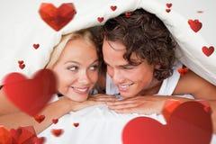 Sammansatt bild av par under ett duntäcke med ett vetande leende Royaltyfri Fotografi