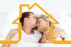 Sammansatt bild av pojkvännen som kysser hennes flickvän i säng Royaltyfri Foto