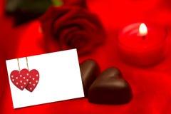 Sammansatt bild av röda rosstearinljus- och chokladhjärtor Arkivbilder