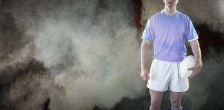 Sammansatt bild av rugbyspelaren som rymmer en rugbyboll Royaltyfri Foto