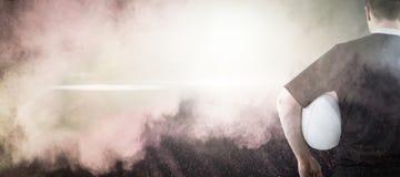 Sammansatt bild av rugbyspelaren som rymmer en rugbyboll Royaltyfri Bild
