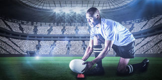 Sammansatt bild av rugbyspelaren som ser bort, medan hålla bollen på att sparka utslagsplatsen med 3d Arkivbild