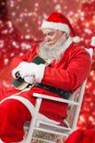 Sammansatt bild av Santa Claus den hållande bibeln, medan koppla av på stol Arkivfoton