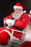 Sammansatt bild av Santa Claus den hållande bibeln, medan koppla av på stol Royaltyfri Bild