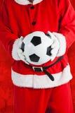 Sammansatt bild av Santa Claus hållande fotboll Arkivfoton