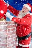 Sammansatt bild av Santa Claus som förlägger gåvaasken in i en lampglas Royaltyfri Foto