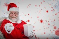 Sammansatt bild av Santa Claus som har popcorn, medan hålla ögonen på tv Royaltyfri Fotografi