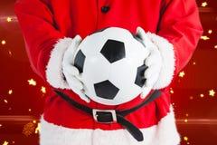 Sammansatt bild av Santa Claus som rymmer en fotboll Arkivbilder