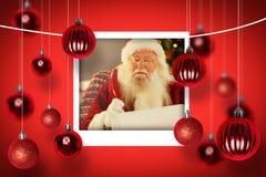 Sammansatt bild av Santa Claus som skriver hans lista med en vingpenna Arkivfoton