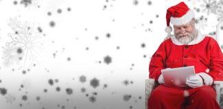 Sammansatt bild av Santa Claus som spelar lekar på den digitala minnestavlan Royaltyfria Foton