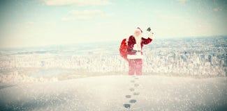 Sammansatt bild av santa som ringer hans klocka Royaltyfria Bilder