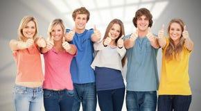 Sammansatt bild av sex vänner som ger upp tummar, som de ler Royaltyfri Foto
