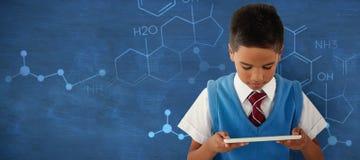 Sammansatt bild av skolpojken som använder den digitala minnestavlan Arkivbilder