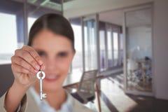 Sammansatt bild av slutet upp av affärskvinnan som visar tangent för nytt hus arkivbild