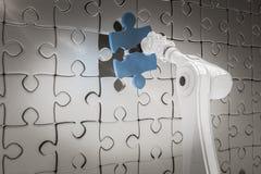 Sammansatt bild av slutet upp av den robotic armen som sätter det blåa figursågstycket på pusslet 3d Arkivbild