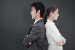 Sammansatt bild av ståenden av allvarligt affärsfolk som står baksida mot baksida arkivfoto