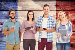 Sammansatt bild av ståenden av att le affärsfolk som använder elektroniska grejer Royaltyfria Bilder