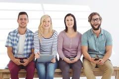Sammansatt bild av ståenden av att le affärsfolk som rymmer elektroniska grejer Fotografering för Bildbyråer