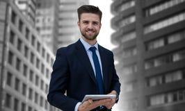 Sammansatt bild av ståenden av att le affärsmannen som rymmer den digitala minnestavlan arkivfoton