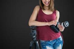 Sammansatt bild av ståenden av att le den hållande kameran för ung fotograf, medan luta på tripoden royaltyfria foton