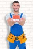 Sammansatt bild av ståenden av den lyckliga modellen för byggnadsarbetareinnehavhus Fotografering för Bildbyråer