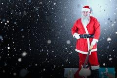 Sammansatt bild av ståenden av det Santa Claus anseendet med gitarr- och gåvaaskar Arkivbild
