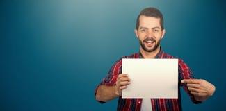 Sammansatt bild av ståenden av den unga mannen som pekar in mot papp mot vit bakgrund Arkivfoton