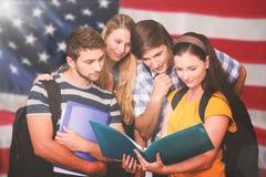 Sammansatt bild av studenter som rymmer mappar på högskolakorridoren royaltyfri fotografi