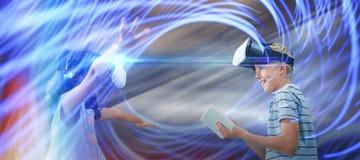 Sammansatt bild av syskon som använder virtuell verklighetexponeringsglas och den digitala minnestavlan Royaltyfri Bild