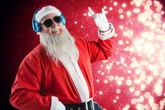 Sammansatt bild av tecknet för Santa Claus visninghand, medan lyssna till musik på hörlurar royaltyfri foto