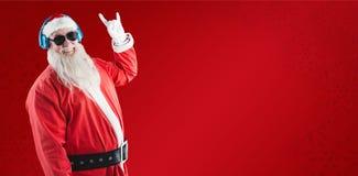 Sammansatt bild av tecknet för yo för Santa Claus visninghand, medan lyssna till musik på hörlurar royaltyfri bild