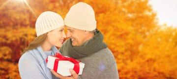 Sammansatt bild av tillfälliga par i hållande gåva för varma kläder arkivbild