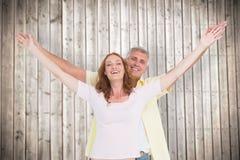 Sammansatt bild av tillfälliga par som ler med lyftta armar arkivbild