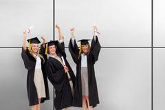 Sammansatt bild av tre studenter i den doktorand- ämbetsdräkten som lyfter deras armar royaltyfria bilder