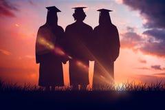 Sammansatt bild av tre studenter i den doktorand- ämbetsdräkten som rymmer ett diplom Royaltyfria Bilder