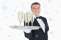 Sammansatt bild av uppassareportionmagasinet mycket av exponeringsglas med champagne Arkivfoto