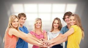 Sammansatt bild av vänner som står runt om de, som de staplar deras händer arkivfoton