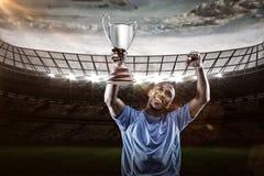 Sammansatt bild 3D av den lyckliga idrottsmannen som ser upp och hurrar, medan rymma trofén Royaltyfri Foto