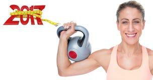 sammansatt bild 3D av lyftande kettlebells för lycklig kvinnlig crossfitter som ser kameran Royaltyfria Foton