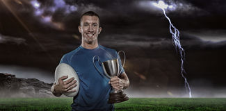 Sammansatt bild 3D av ståenden av att le trofén och bollen för rugbyspelare den hållande Fotografering för Bildbyråer