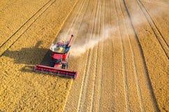Sammanslutningar och traktorer som arbetar på vetefältet Royaltyfri Fotografi