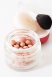 Sammansättning av att brons pärlor och makeup borstar lodlinje Arkivfoto