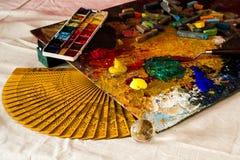 Sammansättning av en konstnärlig palett, en handfan, vattenfärger, akryler, en spatel, en genomskinlig boll och pastell Arkivfoto