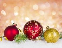 Sammansättning av julgarnering, bollar och gran förgrena sig i snö Royaltyfri Bild