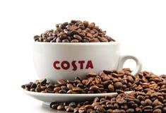 Sammansättning med koppen av Costa Coffee kaffe och bönor Royaltyfria Bilder